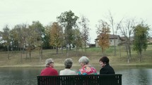 friends sitting on a park bench talking