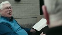 elderly men discussing scripture
