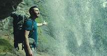 a man walking through a cave under a waterfall