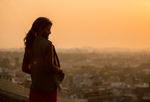 a man standing on a rooftop looking out at a city in India