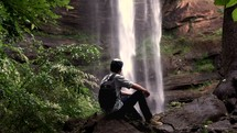 a young man looking at a waterfall