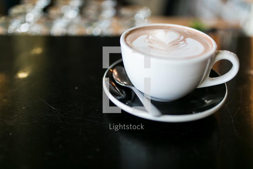 a mug and saucer on the edge of a table