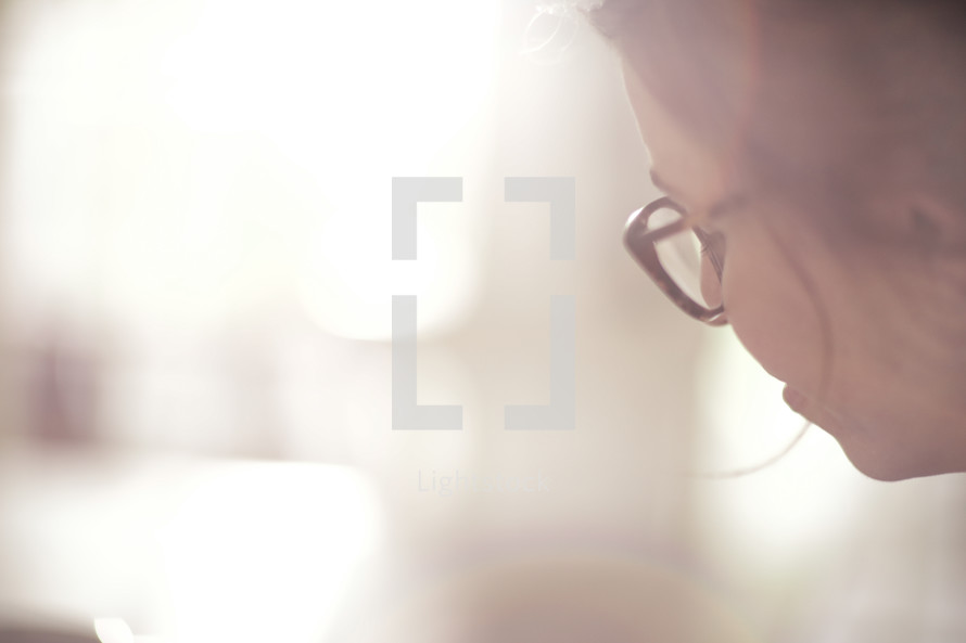 face of a woman wearing reading glasses at a Bible study