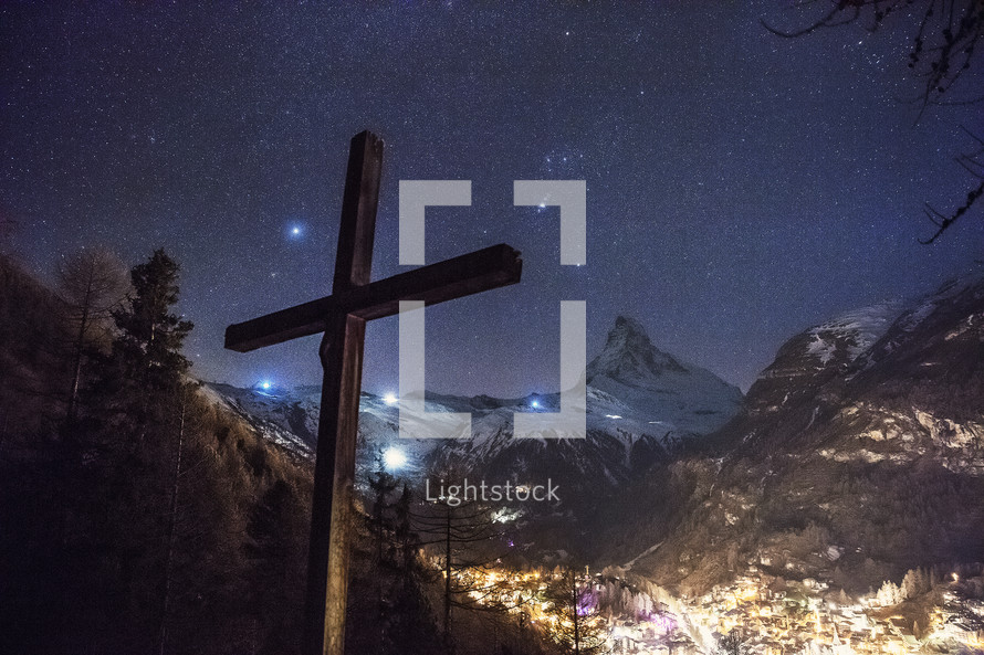 cross in a valley at night with snow