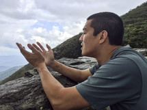man kneeling in prayer on a mountaintop