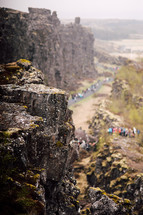 people exploring a paved path along cliffs in Iceland