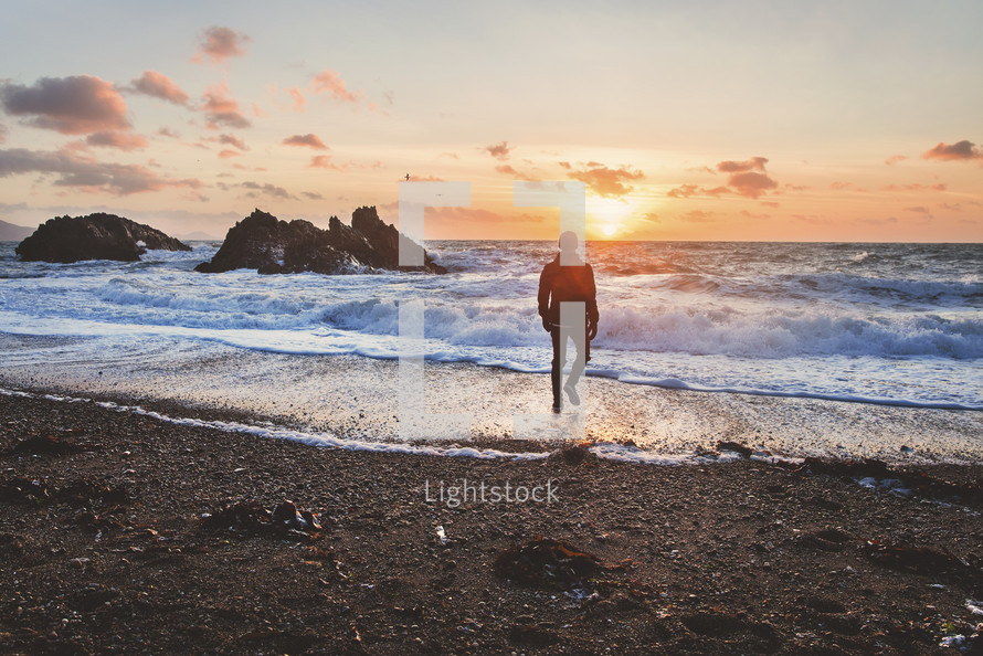 man walking on a beach at sunset in a coat