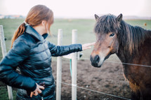 a woman petting a horse