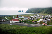 red roof church and homes along a shore in Iceland