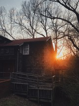 sunset behind a cabin in the woods