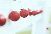 red Christmas ornament balls hanging on a white mantel