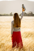 Girl Holding Bible in Air