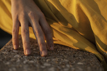 woman's hand touching concrete and fabric of her dress
