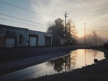 puddle on the side of a rural road and abandoned warehouse buildings at sunrise