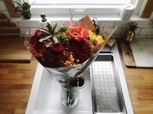 flower bouquet in a vase in a sink