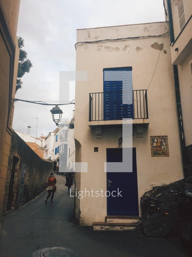 pedestrians walking in an alley between buildings