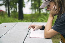 A young woman reading the Bible at a picnic table.