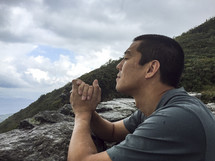 man with praying hands on a mountain top