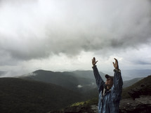 woman on a mountain top with raised hands