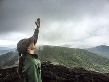 woman with raised hand standing on a mountaintop