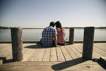 Couple sitting on a pier.