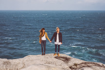 couple holding hands on a rocky beach