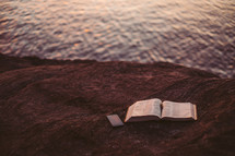 open Bible at the edge of a waterway