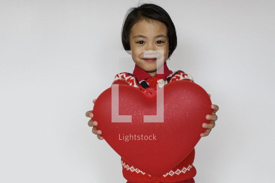a child holding a red heart