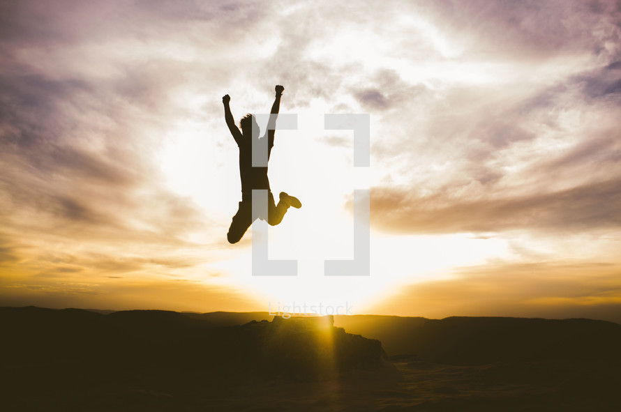 Silhouette of a boy jumping for joy at daybreak.