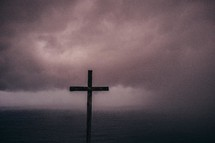Wooden cross in the ocean water covered by low-lying storm clouds.