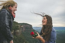 two women on top of a mountain and a rose