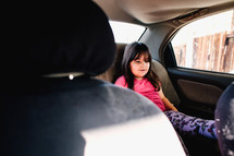 a child in a booster seat in the backseat of a car