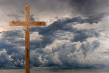 Wooden cross under dark storm clouds.