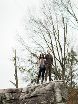 man and woman standing on the edge of a rock