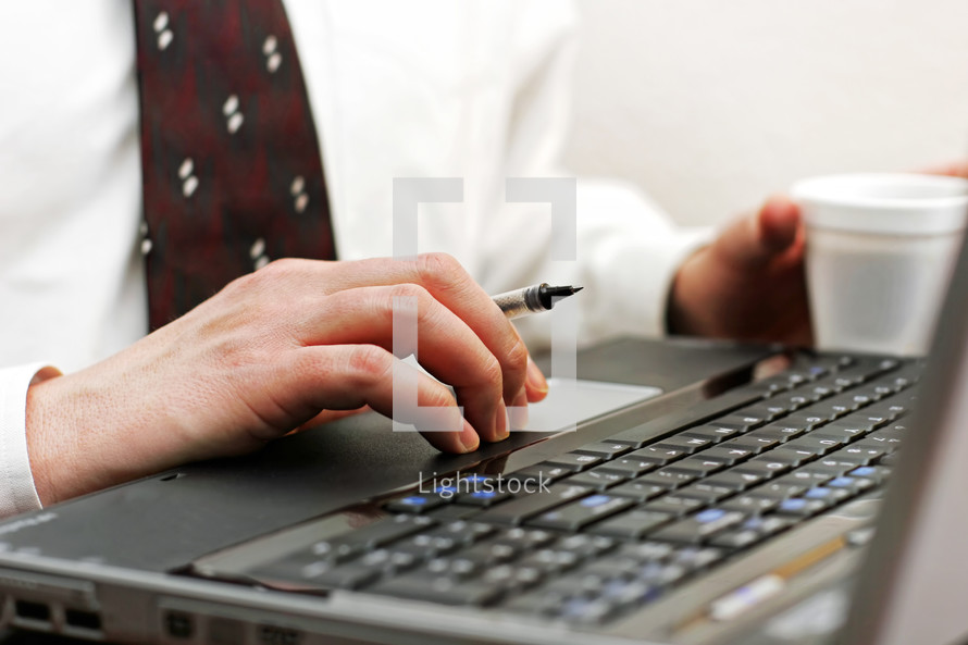 A pastor or businessman in a white shirt and tie, holds a pen in one hand while using a laptop keyboard, and holds a cup of coffee in his other hand.  The image highlights computer connectivity, internet research, productivity, and workplace efficiency.  Main focus point on the foreground hand.
