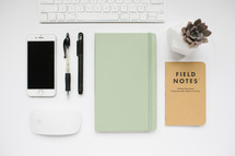 computer keyboard, field notes book, journal, pens, computer mouse, succulent plant, desk, white background