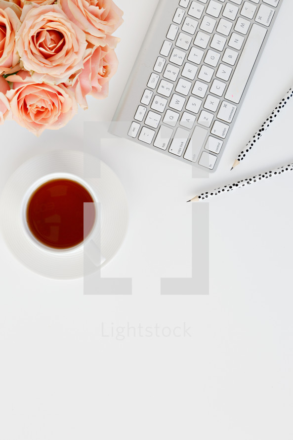 computer keyboard, pencils, tea cup, and peach roses on a desk