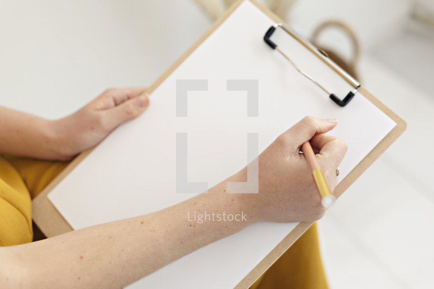 a woman writing on a clipboard