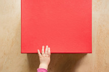 a girls hand on a red box