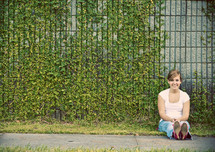 Woman sitting in front of ivy covered wall