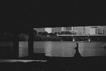Bride walking under a bridge