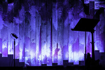 Music stand and microphone on stage with blue and purple illuminated backdrop.