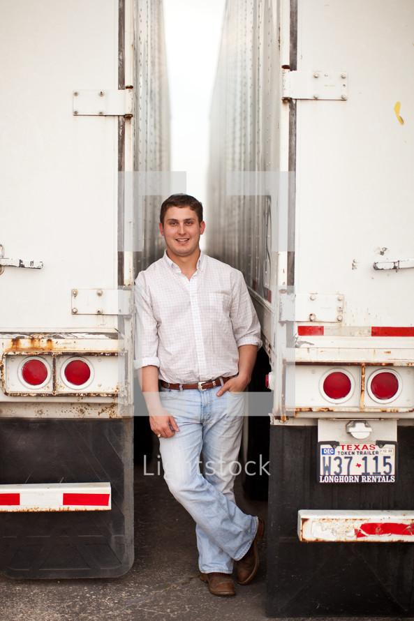 man standing between two tractor trailer trucks