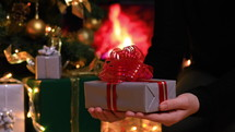 placing a Christmas gift under the Christmas tree