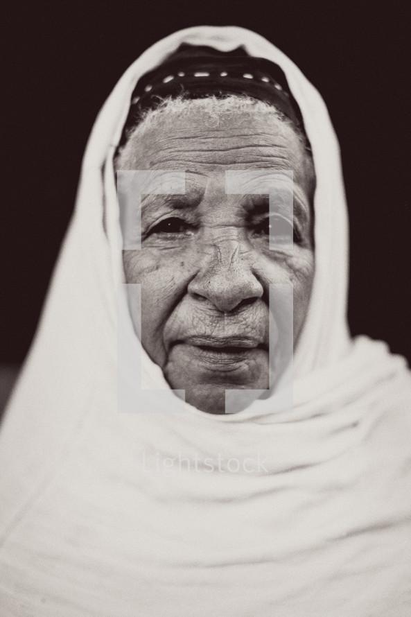 shrouded elderly woman
