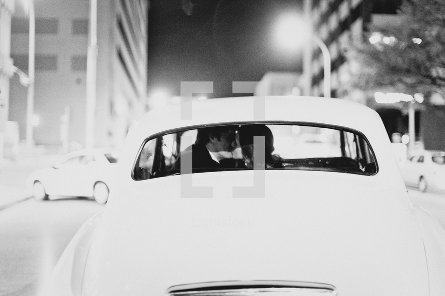 A married couple kissing as they drive away from their wedding