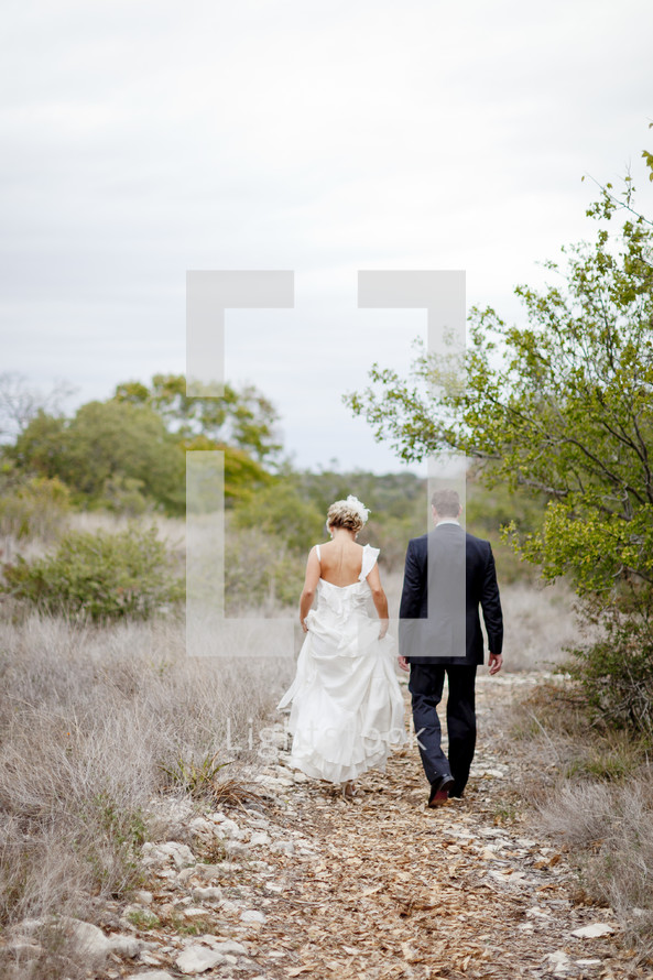 bride and groom walking down an outdoor trail