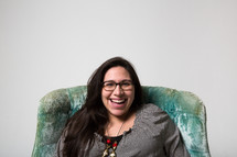 Laughing woman in a green chair.