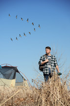 "a young man walking outdoors near a tent and geese flying in a ""V"""