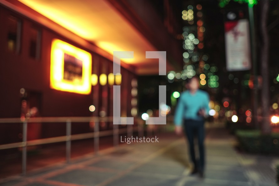blurry image of a man on a city sidewalk at night